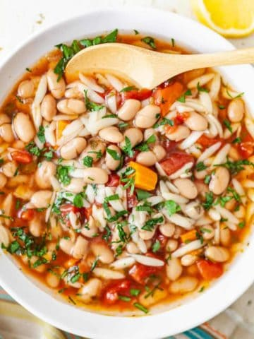A bowl of Slow Cooker White Bean & Tomato Soup with Orzo garnished with parsley