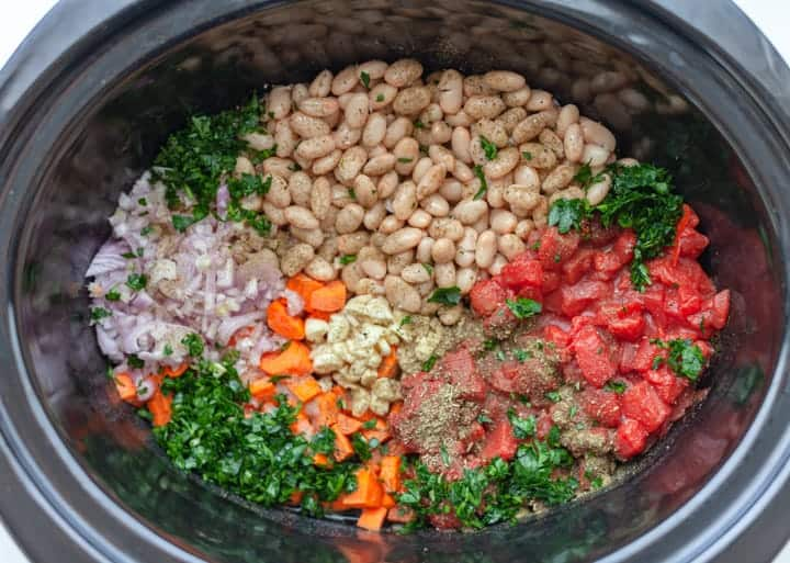 Raw ingredients for Slow Cooker White Bean and Orzo in a crockpot: carrots, canned tomatoes, white beans, onion, garlic, parsley and spices