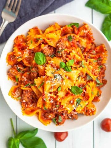 A white bowl filled with Instant Pot bowtie pasta cooked in a bolognese sauce topped with grated cheese and basil