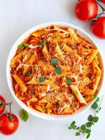 White bowl filled with Instant Pot Chicken Parmesan Pasta made from penne pasta, tomato sauce, chicken tenders and melted cheese topped with crunchy breadcrumbs