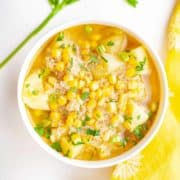 Bowl of corn, potato and quinoa soup garnished with parsley with a bright yellow napkin next to the bowl