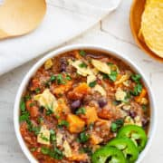 Bowl of Quinoa Sweet Potato Chili garnished with sliced jalapeno, herbs and tortilla chips