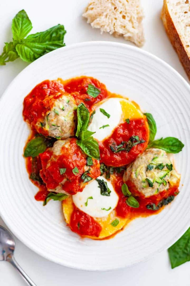 Plate of turkey and zucchini meatballs, rounds of polenta, melted mozzarella, tomato sauce and basil