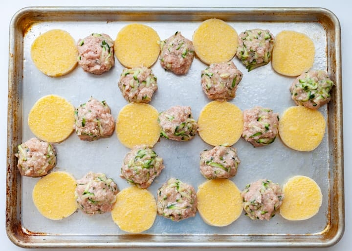 A sheet-pan of raw turkey and zucchini meatballs with rounds of polenta,