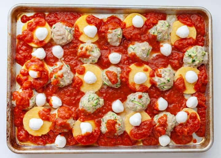 Sheet-pan of meatballs and round slices of polenta with raw mozzarella and tomato sauce