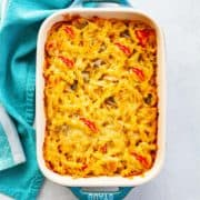 Casserole dish of baked fusilli chicken fajita pasta with melted Monterey Jack cheese