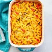 Casserole dish of baked fusilli chicken fajita pasta with melted Monterey Jack cheese