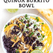 A bowl of Instant Pot Brown Rice & Quinoa topped with grated cheddar, black beans, green onion and sliced lime