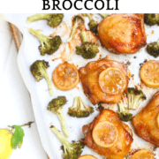 A sheet-pan with cooked chicken thighs, lemon slices and broccoli