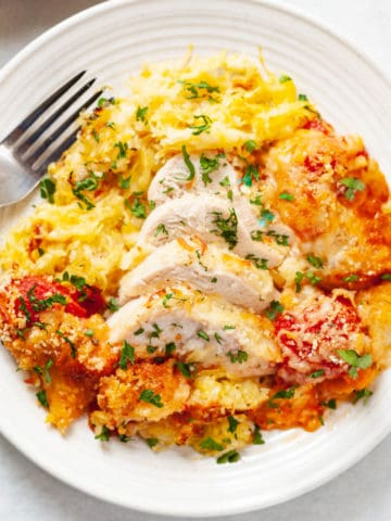 plate of sliced chicken breast and roasted spaghetti squash with tomato sauce, mozzarella, panko and parmesan