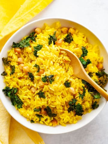 Bowl with yellow turmeric coconut rice, kale and chickpeas