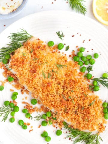 A piece of cod on a plate with panko baked on top, surrounded by peas