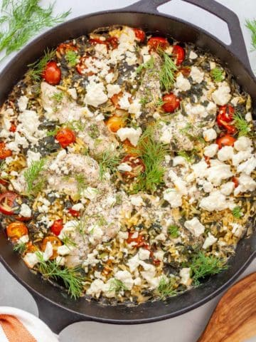 Cast iron skillet of baked orzo and chicken tenders with feta, tomatoes, spinach & dill