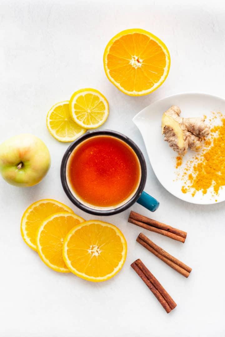 A mug of tea surrounded by orange and lemon slices, cinnamon sticks, turmeric, ginger and an apple