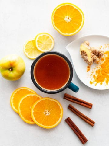 A mug of tea surrounded by orange and lemon slices, cinnamon sticks, turmeric, ginger and an apple