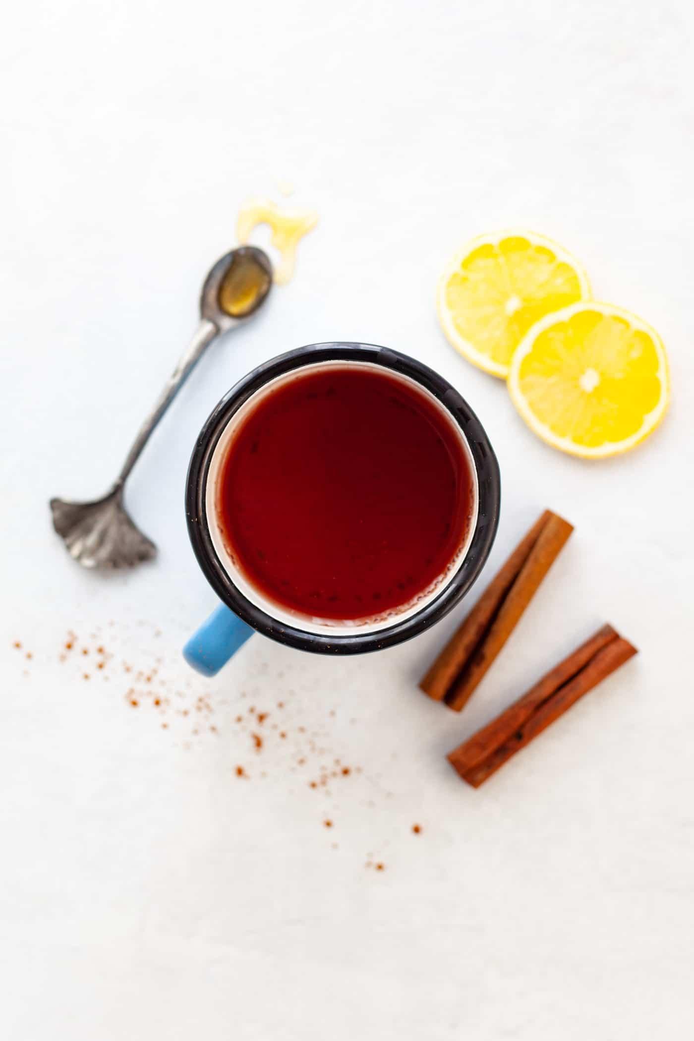 mug of cinnamon tea surrounded by cinnamon sticks, lemon and honey