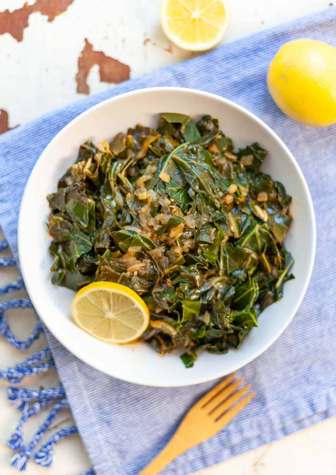 bowl of cooked collard greens topped with chopped onion
