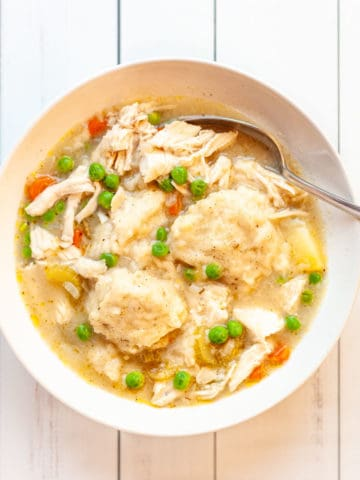 A bowl of shredded chicken breast, peas, carrots, potatoes and dumplings in broth