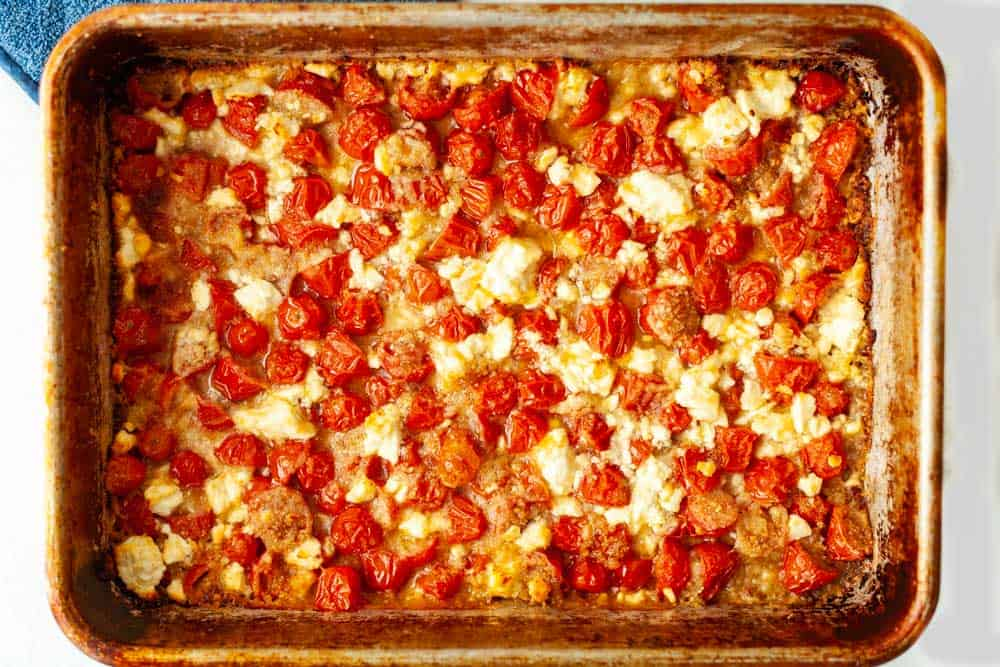 baking pan of cherry tomatoes and garlic baked with feta