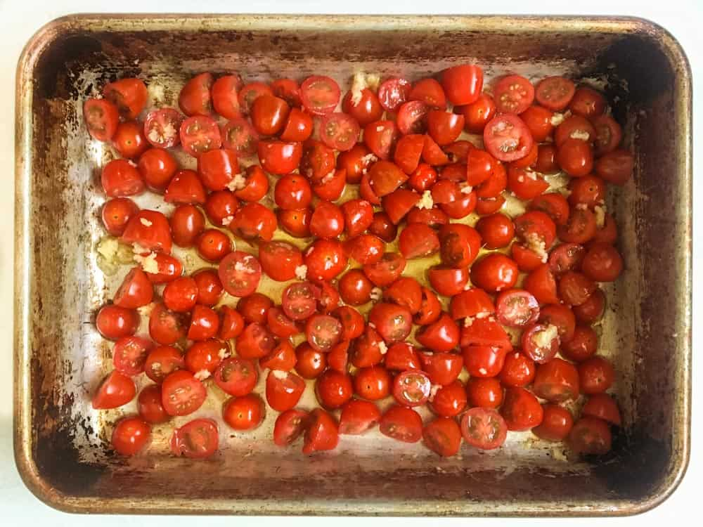 baking pan of halved cherry tomatoes, olive oil and garlic
