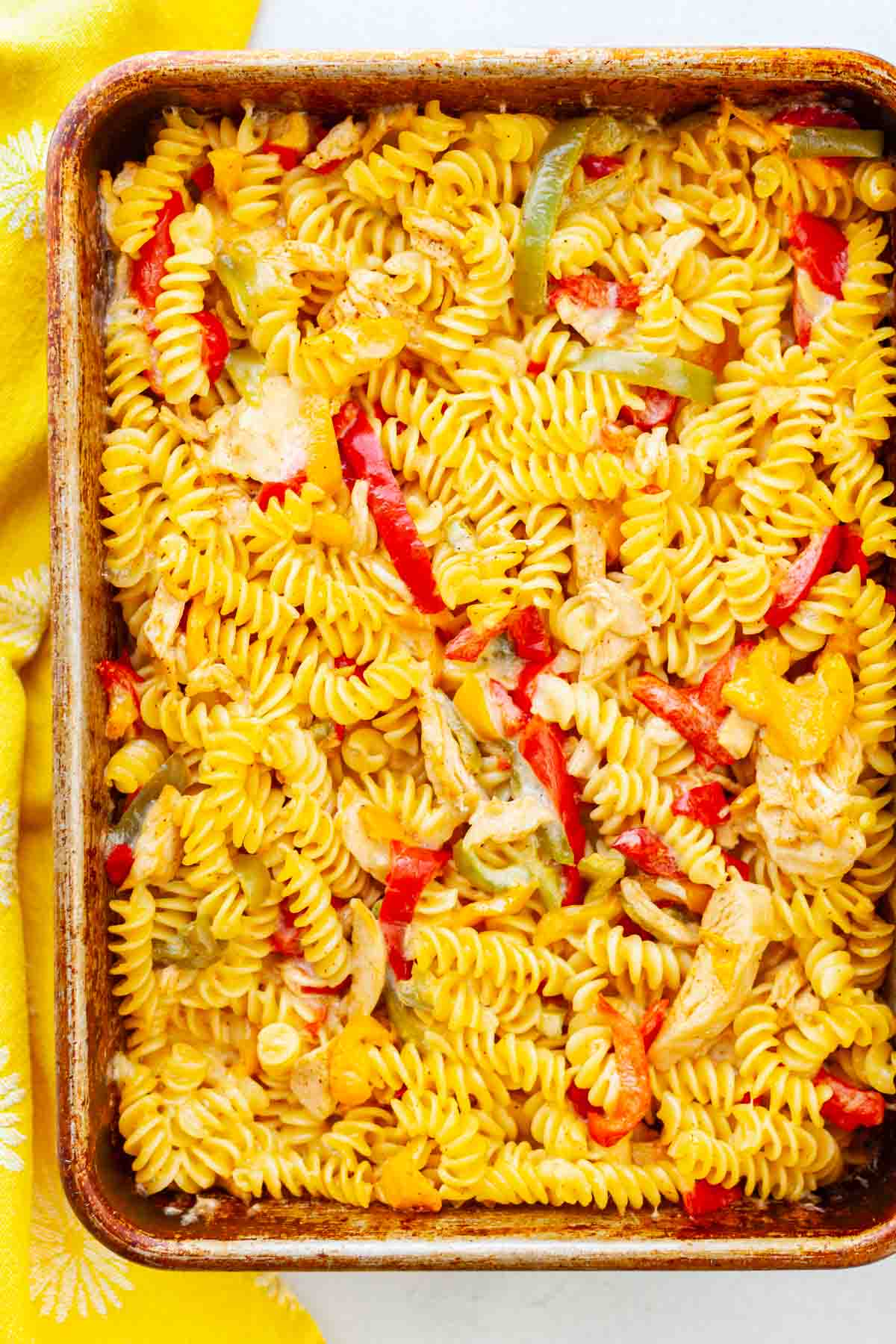 pan of baked rotini pasta with chicken and bell peppers