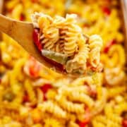 spoon with a scoop of cheesy rotini noodles with chicken and bell pepper