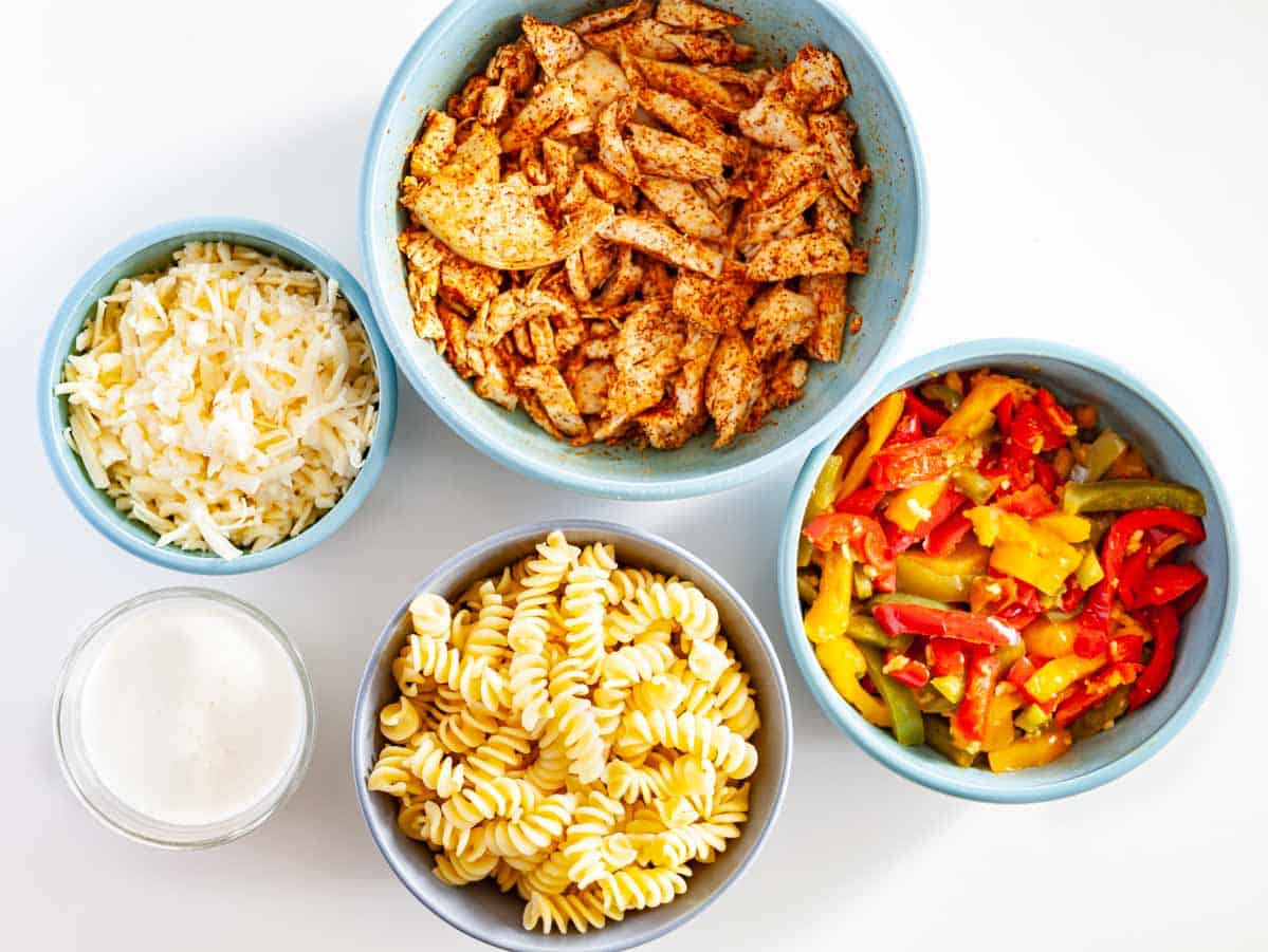 bowls of grated cheese, cream, shredded chicken, chopped bell pepers and rotini pasta