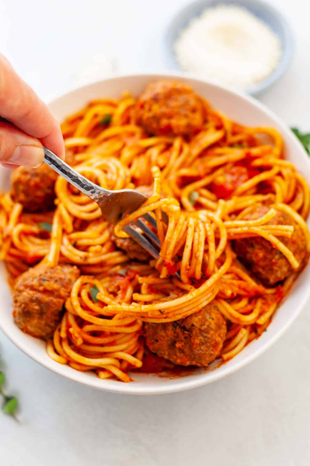 bowl of spaghetti twirled around a fork and meatballs in red sauce