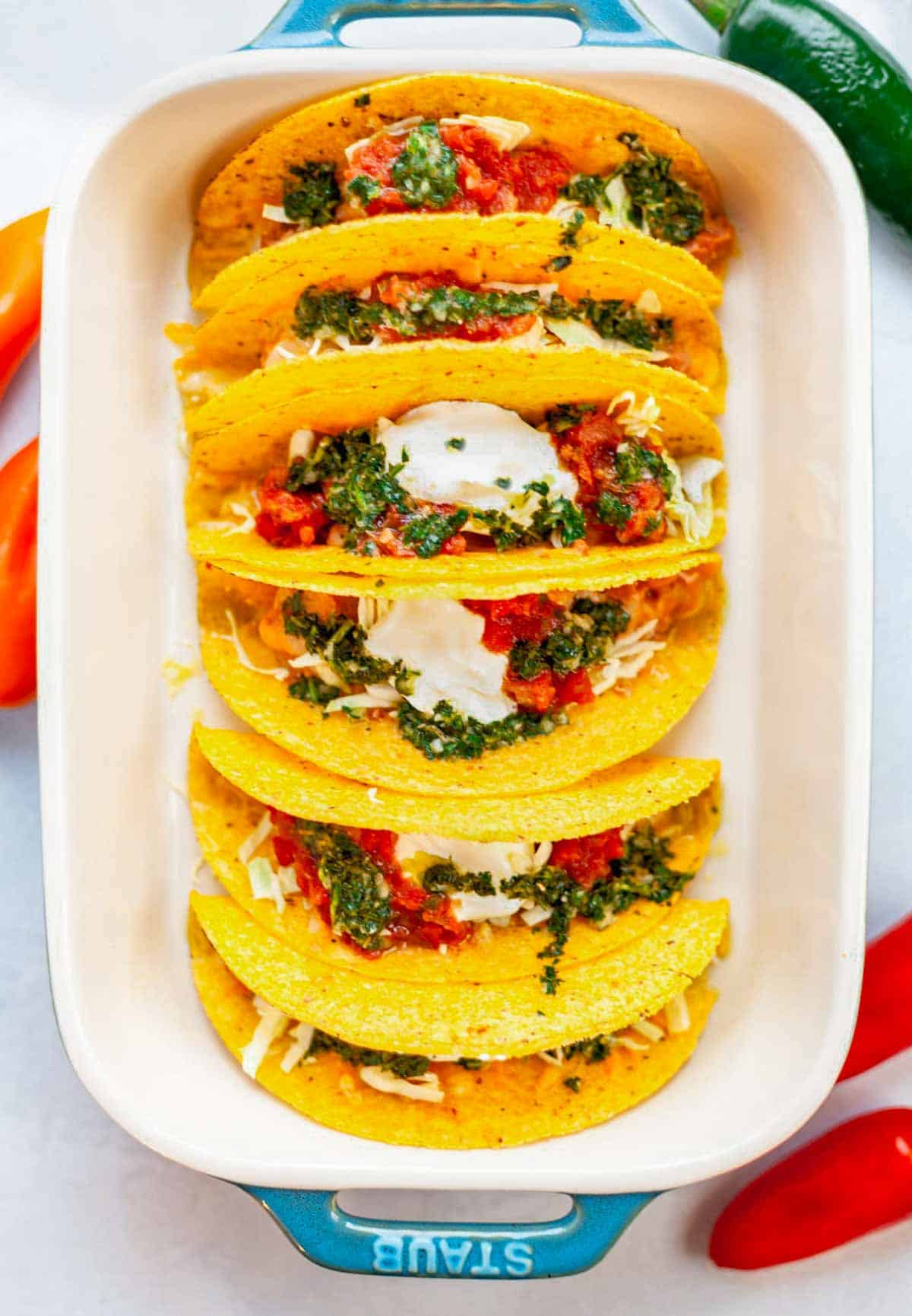 hard taco shells in a pan filled with refried beans, melted cheese, salsa and cilantro