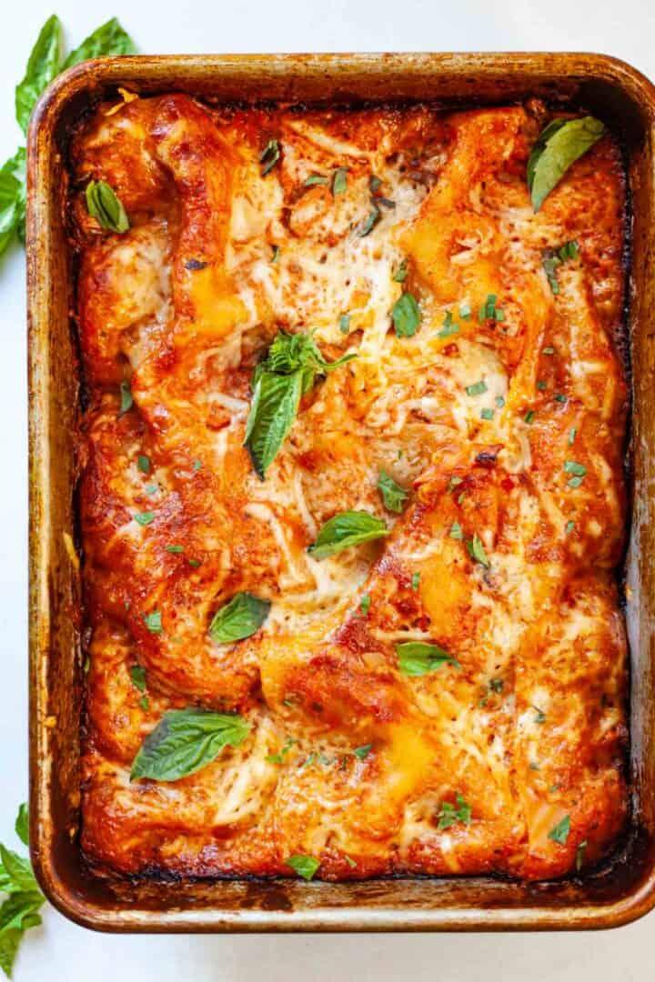 a baking dish of cheesy lasagna with fresh basil leaves