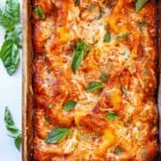 a baking dish of lasagna with fresh basil leaves
