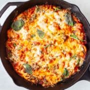butter beans in a cast iron skillet baked under melted cheese, tomato sauce and basil