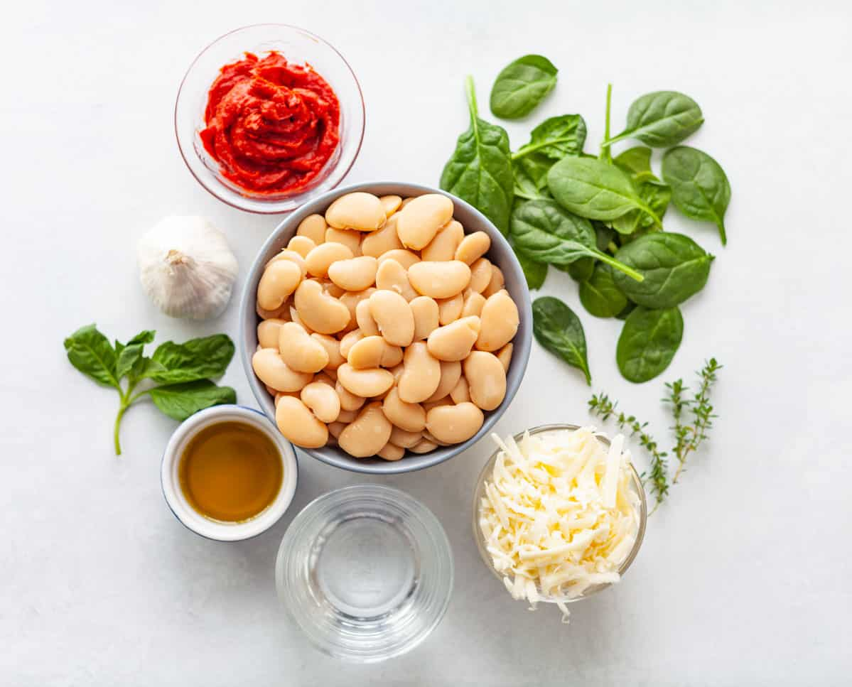 ingredients on a white background: canned butter beans, baby spinach, tomato paste, olive oil garlic, grated cheese and water