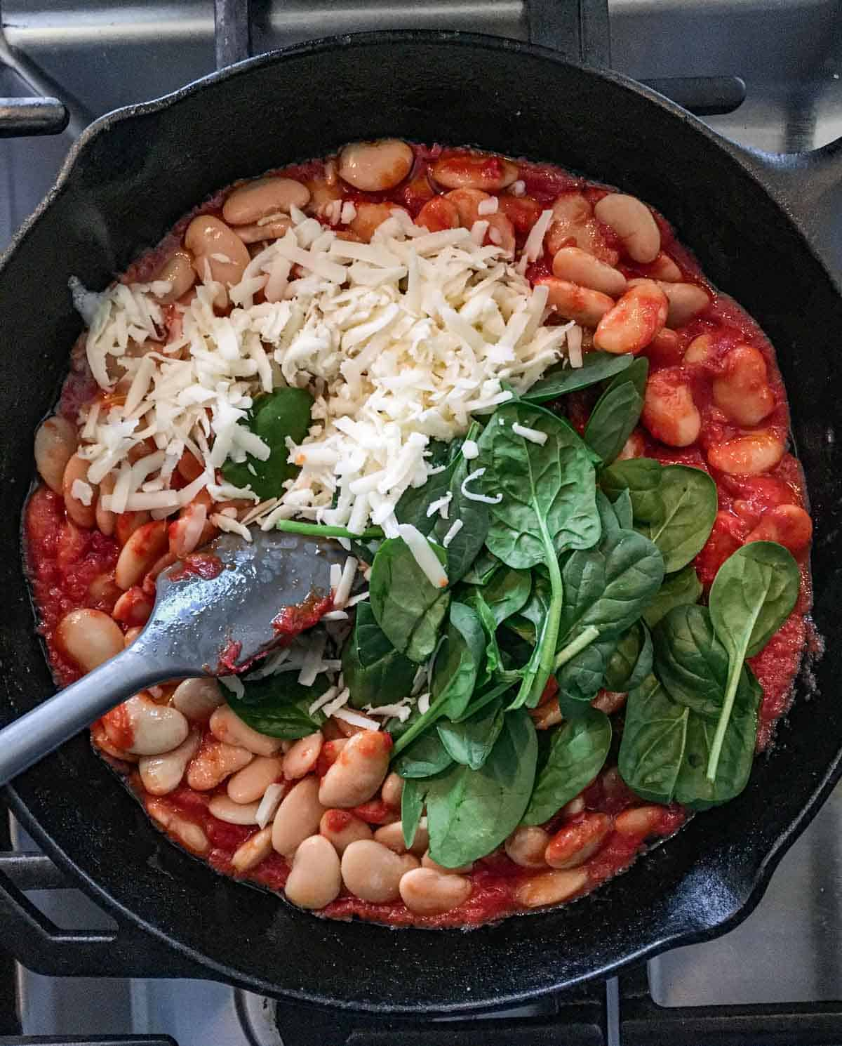 cast iron skillet filled with canned butter beans, tomato paste, spinach and grated cheese