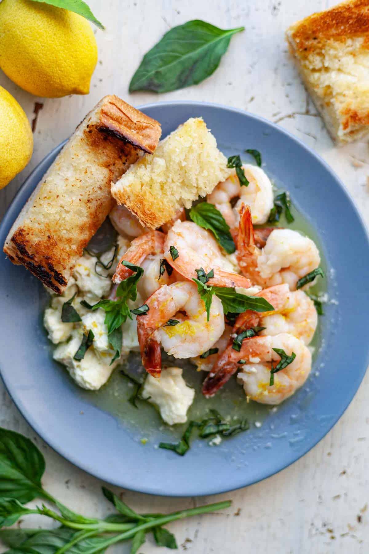 a small blue plate with cooked shrimp with feta and basil and two slices of garlic bread