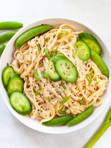 bowl of pasta in creamy tahini sauce garnished with sliced cucumbers and raw snap peas