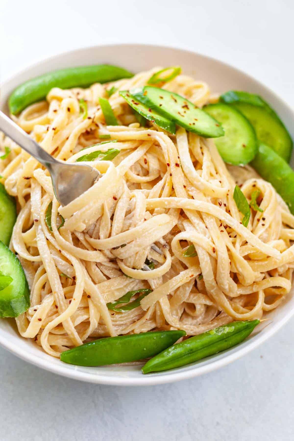 closeup of pasta in creamy tahini sauce swirled around a fork