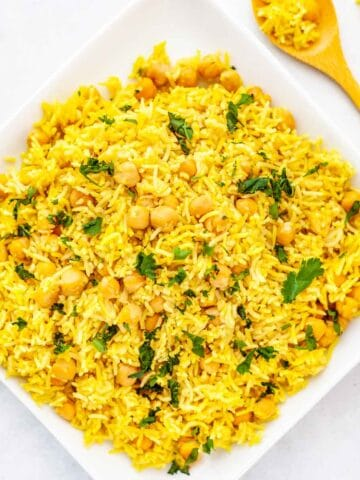 fluffy basmati rice and chickpeas on a plate, seasoned with yellow turmeric and other spices