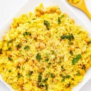 basmati rice and chickpeas on a plate, seasoned with yellow turmeric and other spices