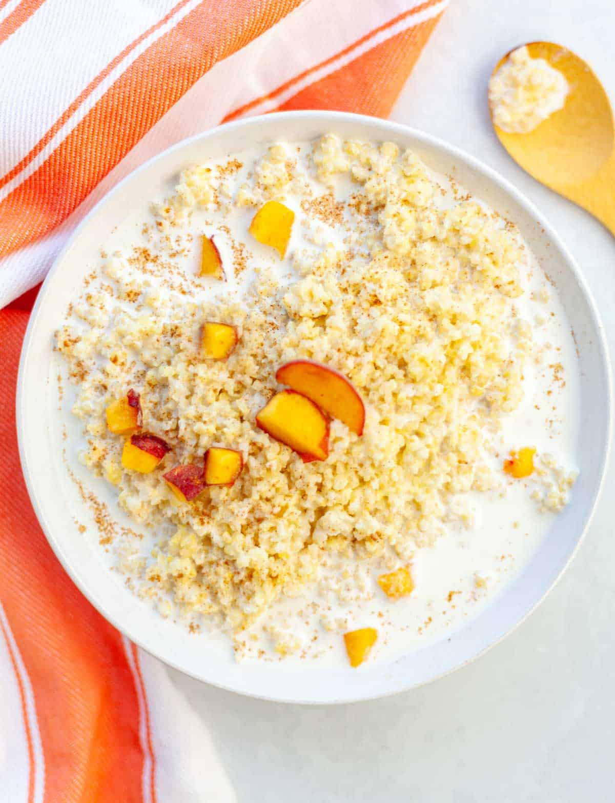 bowl of millet porridge with milk, peaches and cinnamon
