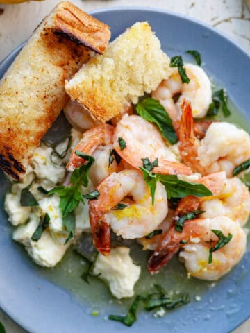 cooked shrimp on a plate with basil and feta cheese with two slices of bread