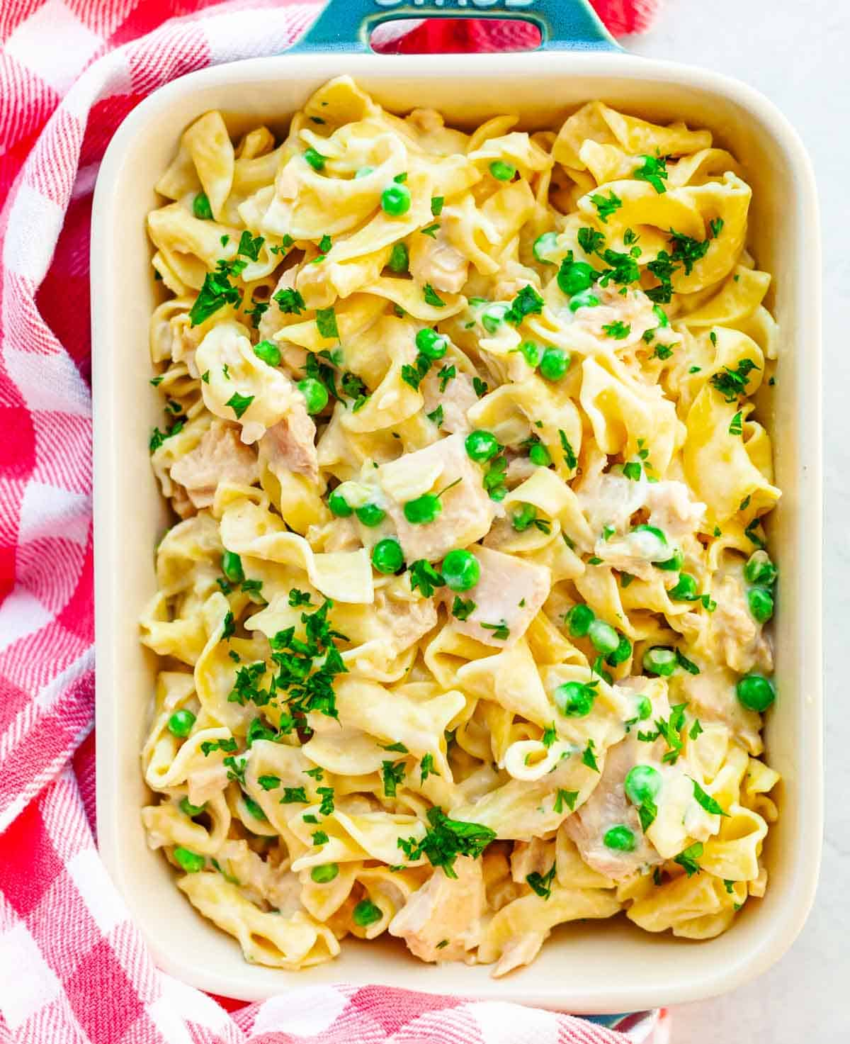 baking dish filled with tuna casserole with egg noodles and peas