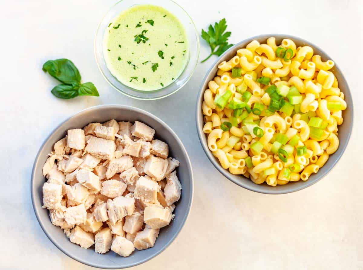3 bowls of ingredients for macaroni and chicken salad: chopped chicken breast, cooked macaroni and green goddess dressing
