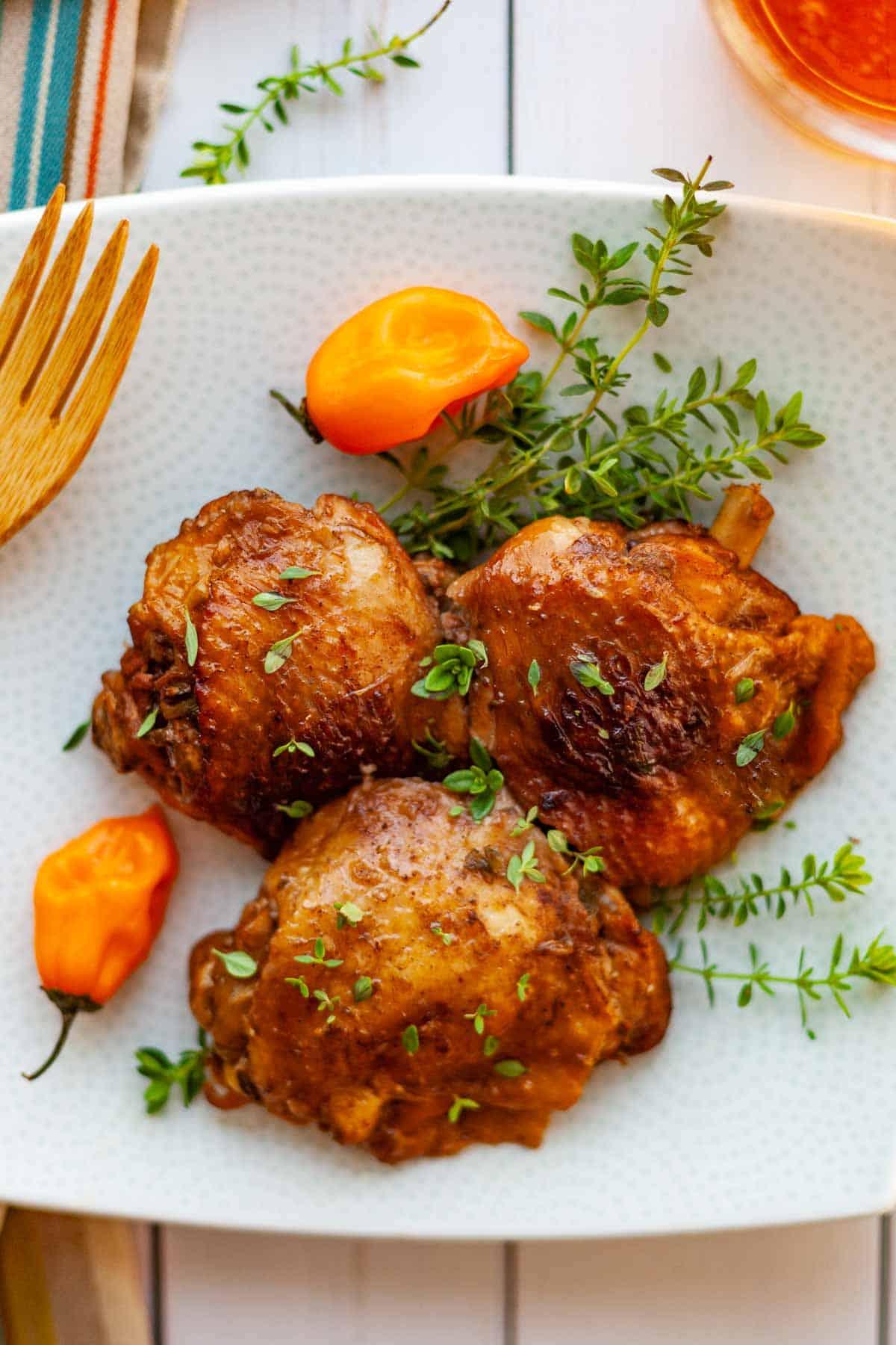 three bone-in chicken thighs cooked in a jerk chicken marinade