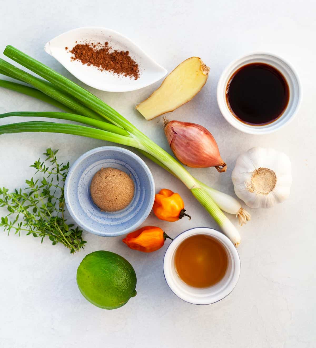 ingredients for jerk chicken, such as lime, ginger, garlic, hot pepper, green onion, shallot, brown sugar, soy sauce, thyme and vinegar