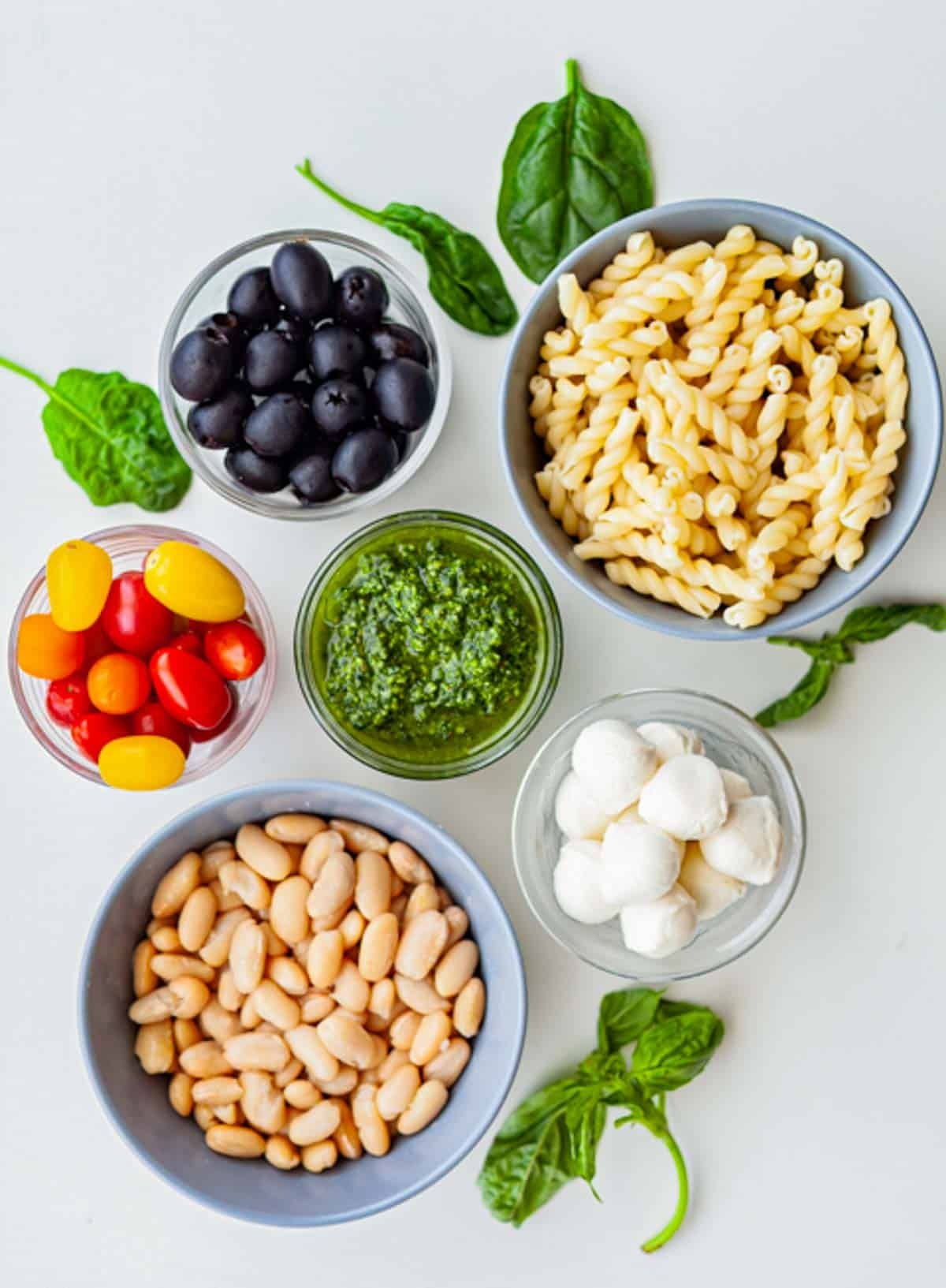 bowls of ingredients for pasta salad, including white beans, olives, pasta, mozzarella and pesto