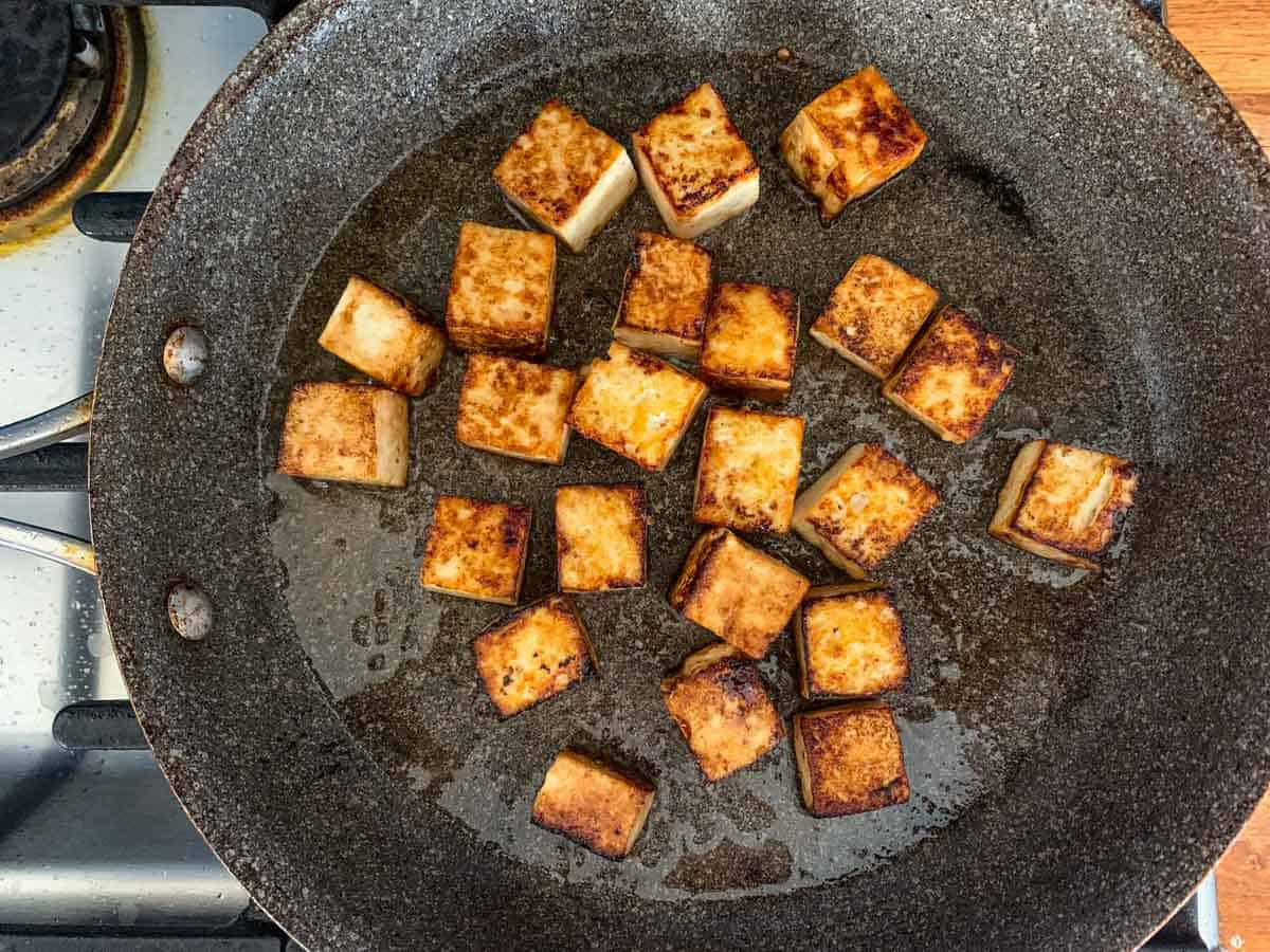 tofu cubes searing in a skillet