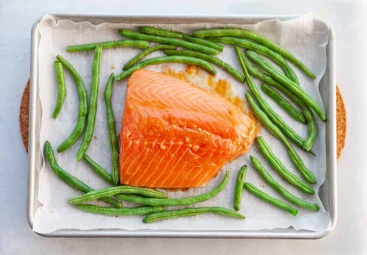 uncooked salmon and green beans on a sheetpan