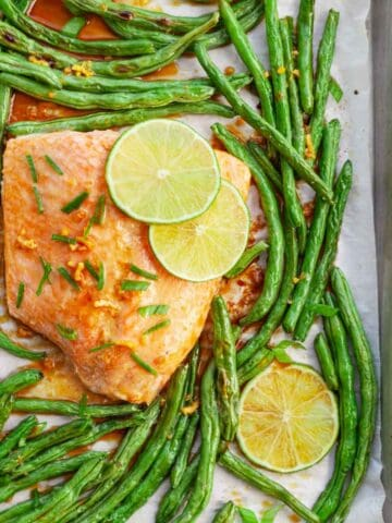 cooked green beans and salmon on a sheet pan with slices of lime