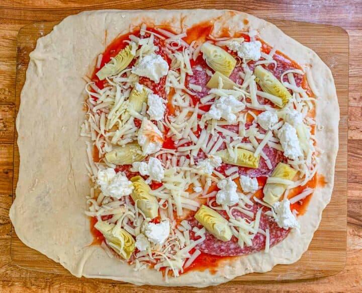 uncooked pizza dough with mozzarella, ricotta, salami and artichoke heart